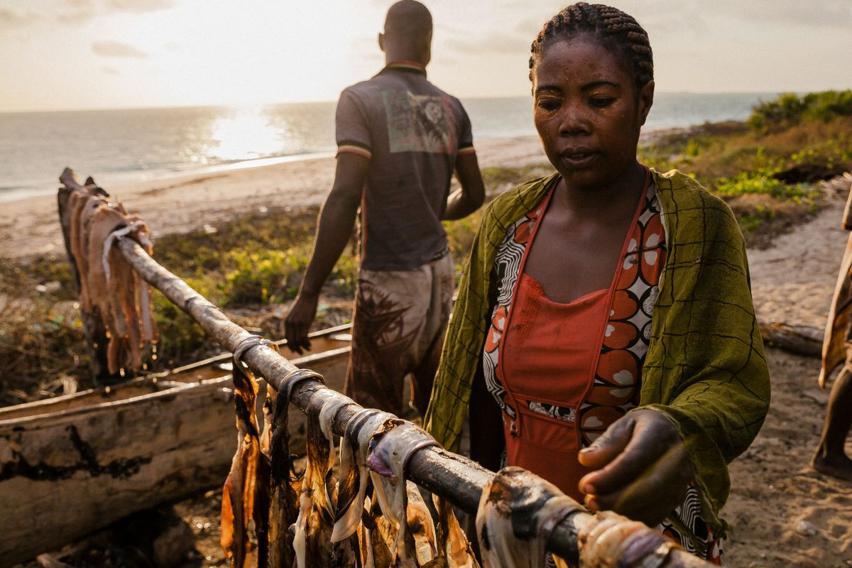 A migrant woman hangs salted octopus and shark meat out to dry before taking it to market