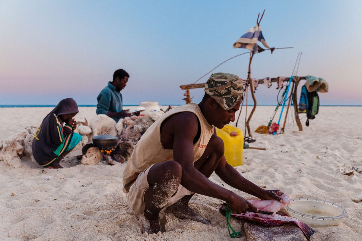 A fisherman fillets fish for supper at his camp on a sandbar.