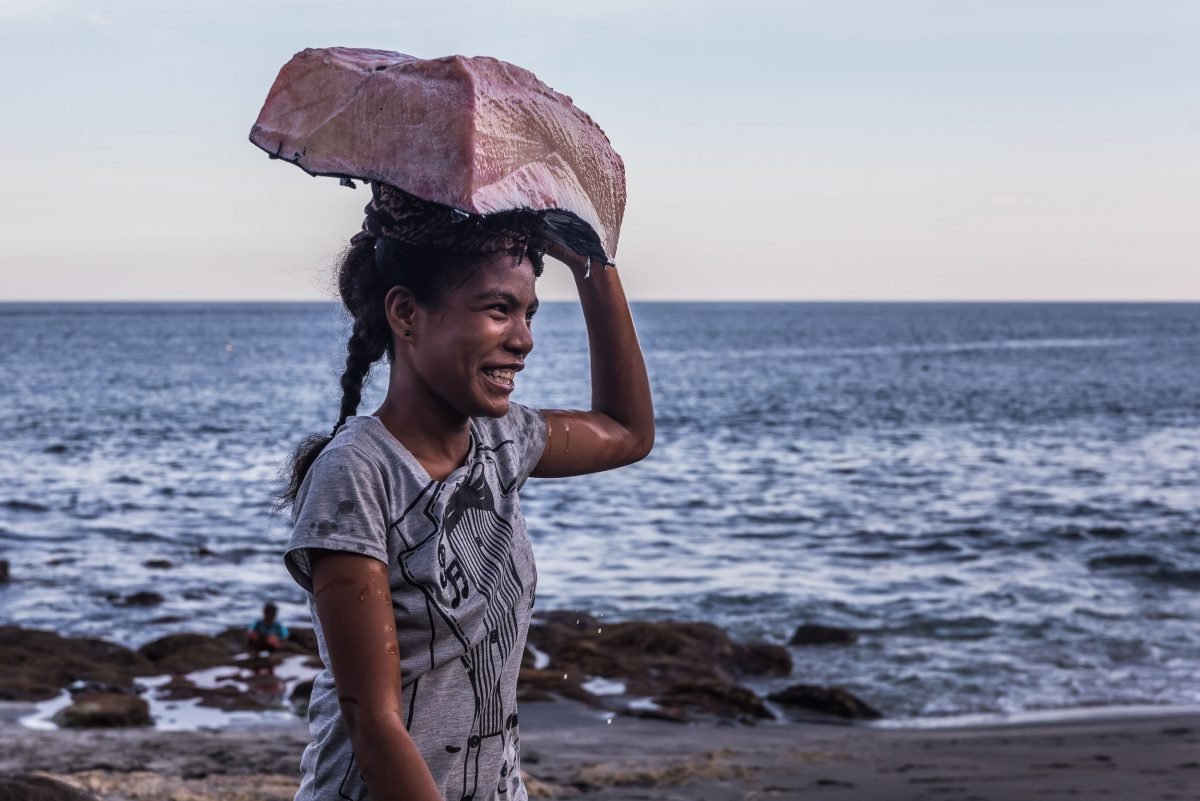 an Indonesian woman carries whale meat on her head
