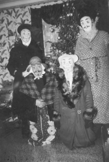 "Mummers wear their ""false faces"" in Winterton, Newfoundland and Labrador, in 1958. Photo courtesy of the Wooden Boat Museum of Newfoundland and Labrador"
