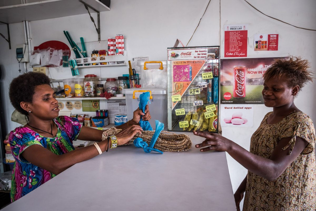 woman buying tabu shell money at a shop