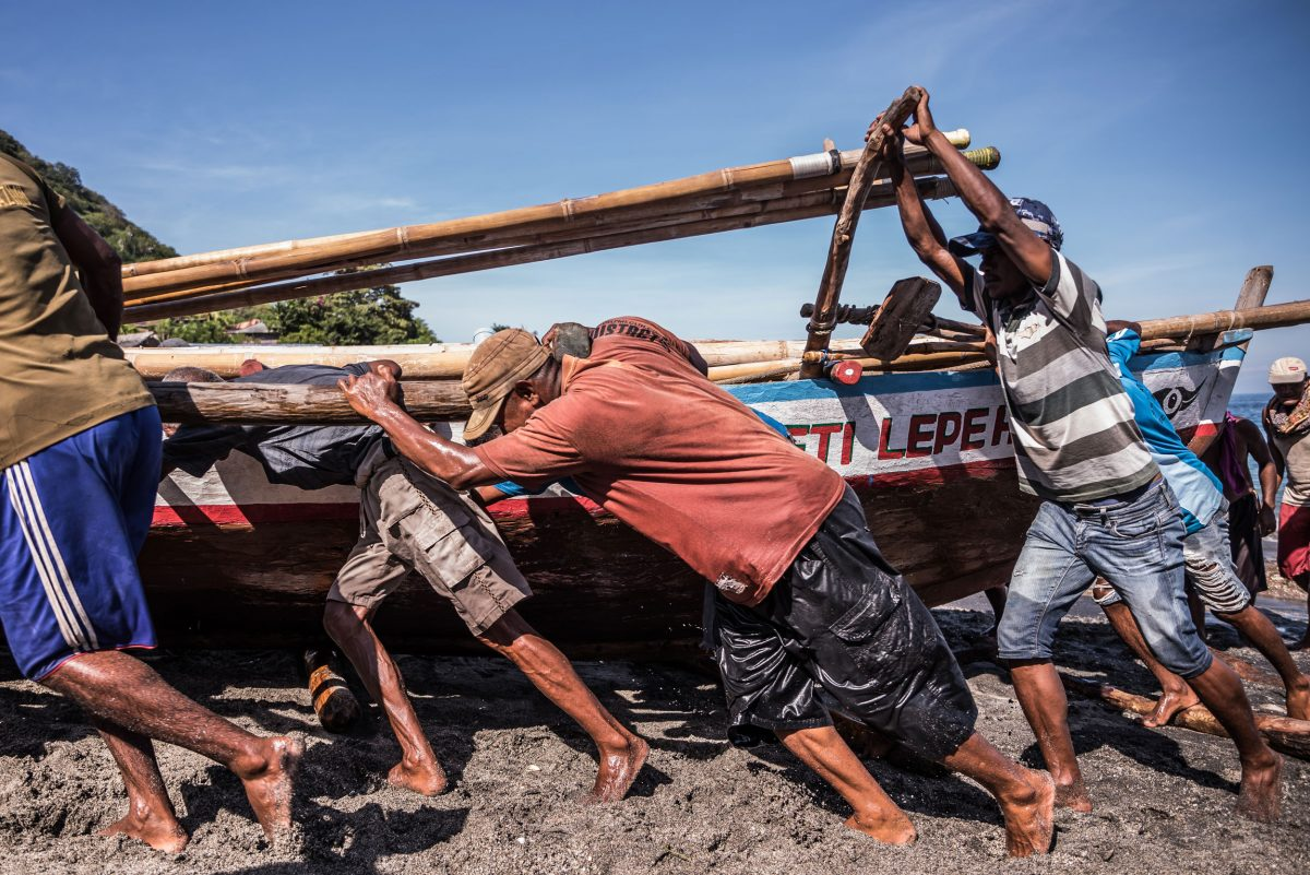 villagers pushing a fishing boat