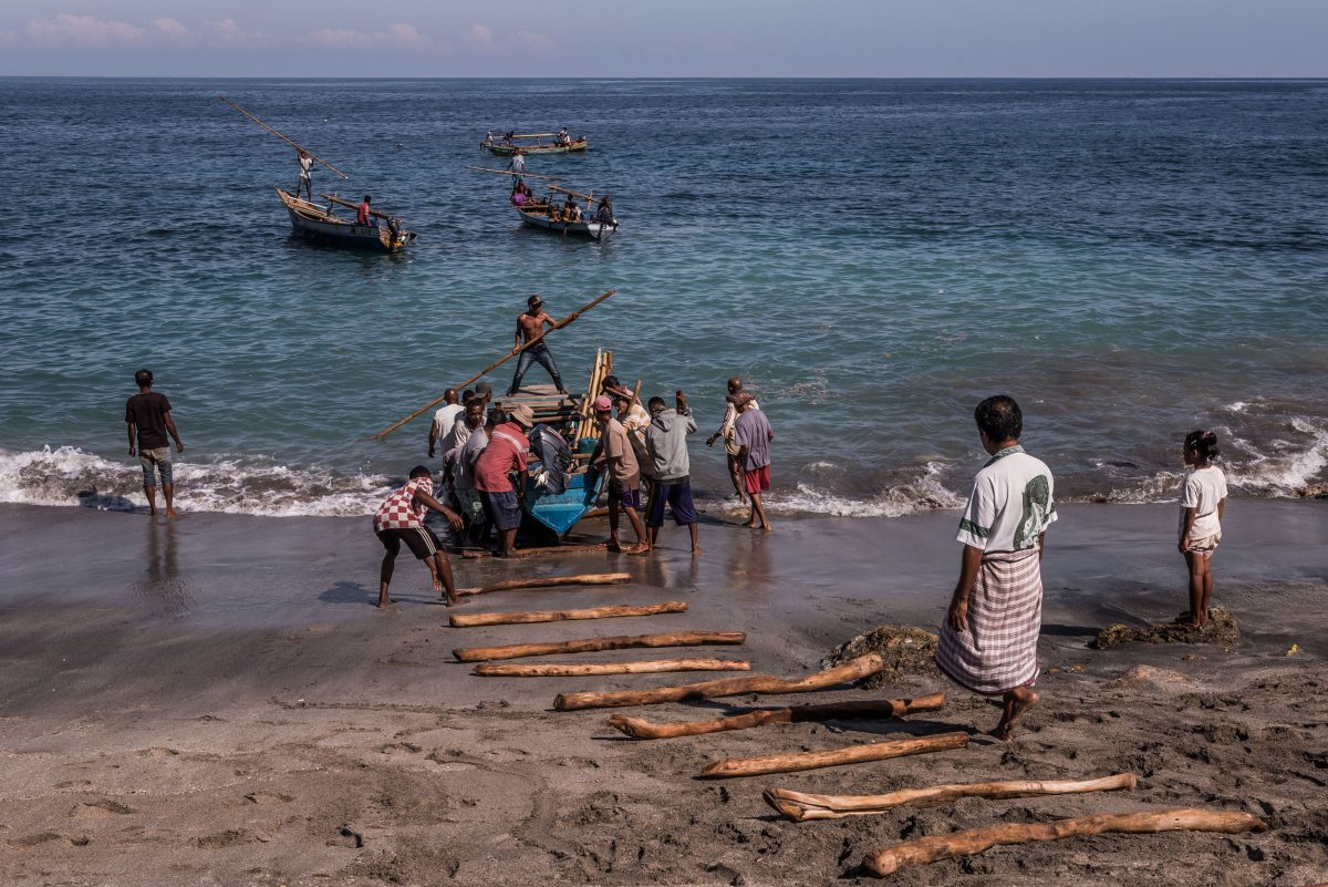 Villagers launch a fishing boat