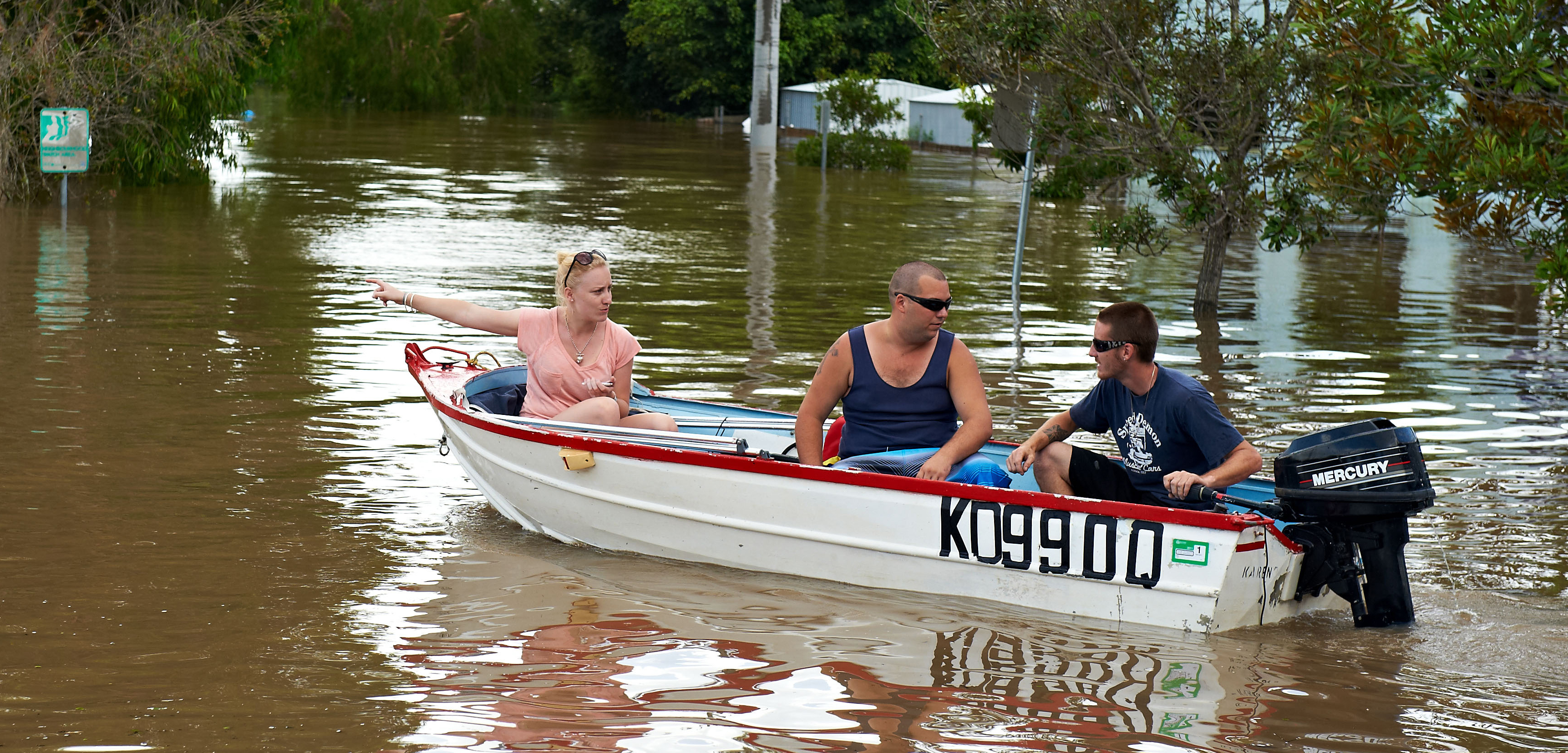 Three people navigate the flood waters in Brisbane, Australia, after heavy flooding hit the region in 2011. Photo by Mark Nemeth/Alamy Stock Photo