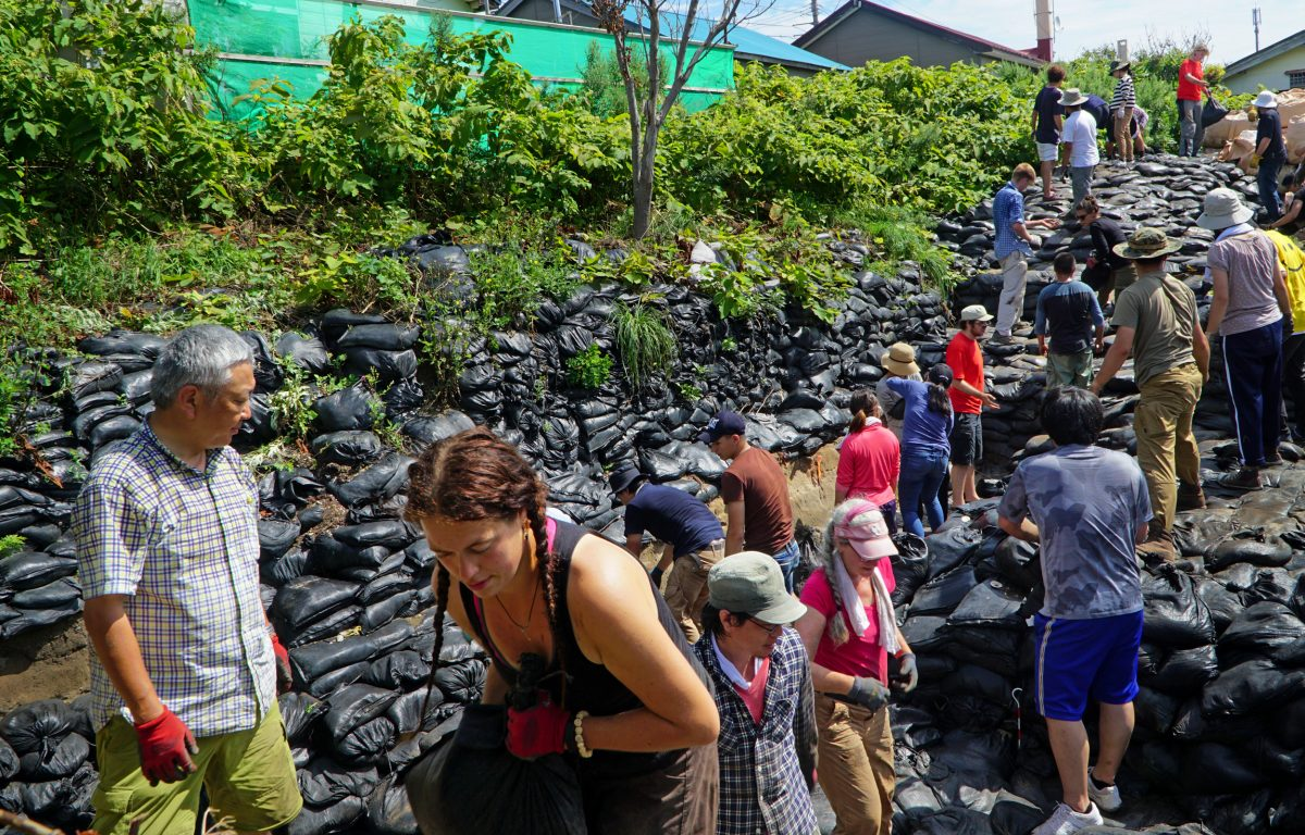 On Rebun Island, off the coast of Hokkaido, Hirofumi Kato, left, Zoe Eddy, foreground, and volunteers pile sandbags on the Hamanaka II archaeological site, where they will stay until the dig continues the following year. Photo by Jude Isabella
