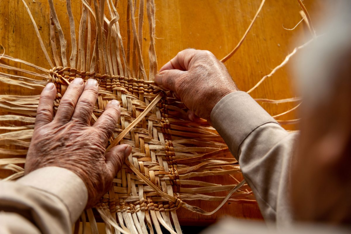 Ed Carriere weaving the base of a basket