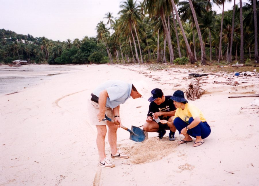 Robert Higgins (left) takes a sample on the beach with colleagues.