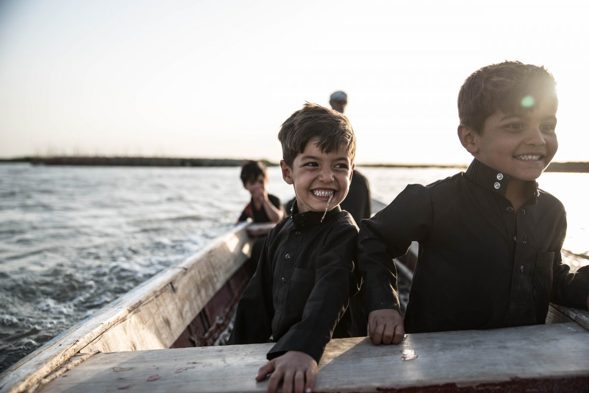 Muhammad (left) and Sajjad Ali laugh during a boat ride to visit their cousins in the Central Marsh. Photo by Emilienne Malfatto