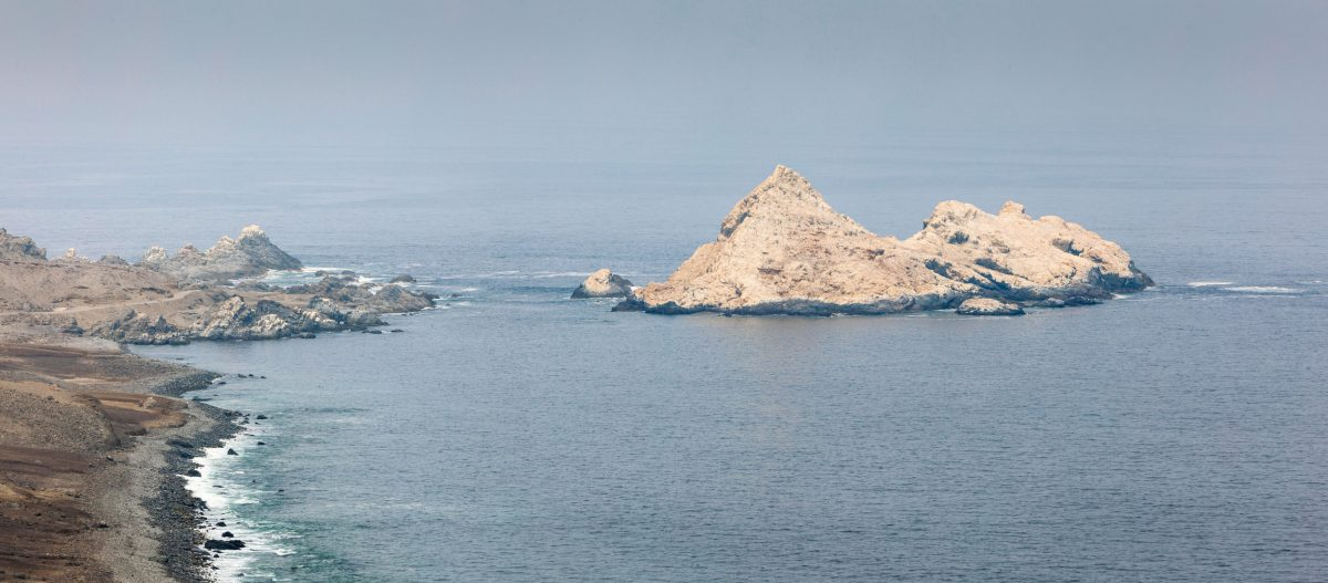 Rocky coast of northern Chile with bird island covered with guano