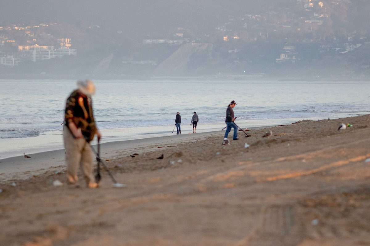 metal detectorists on Santa Monica Beach at sunrise