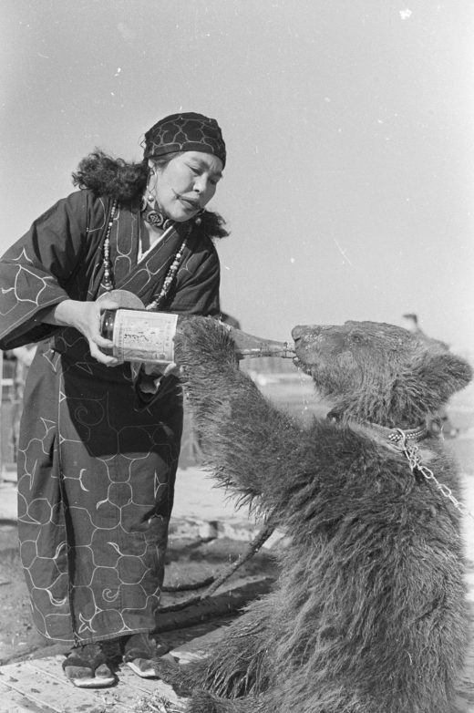 Taken in 1955, this photo shows an Ainu woman feeding a bear cub. The Ainu raised bear cubs as they would a member of the family, until the <em>iyomante</em>, the bear-sending ceremony. Photo by Evans/Three Lions/Getty Images
