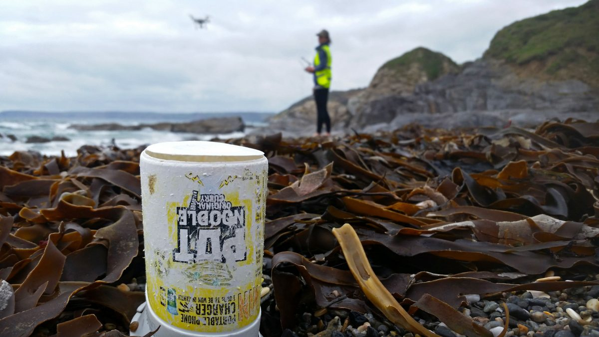 A plastic noodle pot litters Hemmick Beach in Cornwall, England, as Ellie Mackay, cofounder of the Plastic Tide, uses a drone to document plastic debris in the distance. Photo by the Plastic Tide