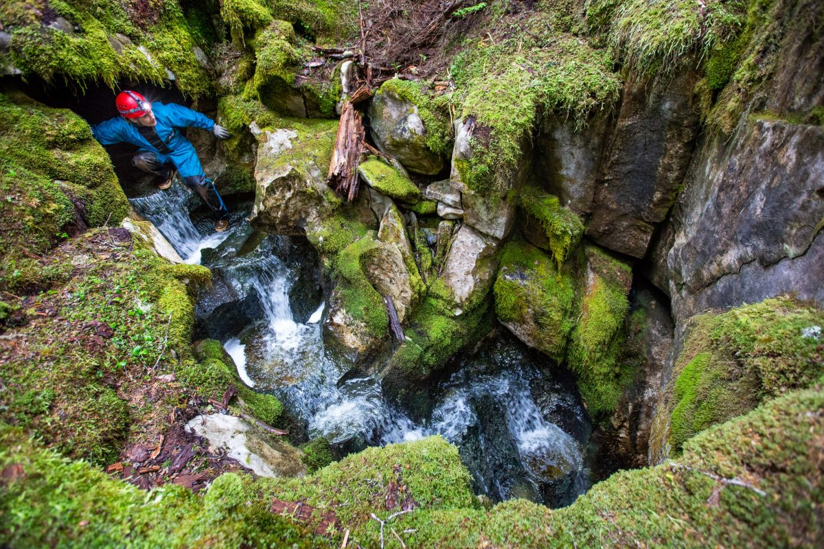 A scientist scrambles over rocky terrain where a river flows out of rock and then back into it.