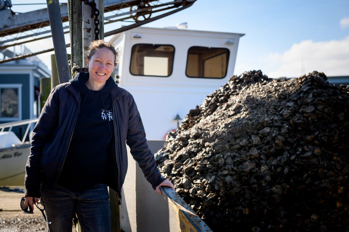 Fiona Lewis poses next to a mound of oyster spat