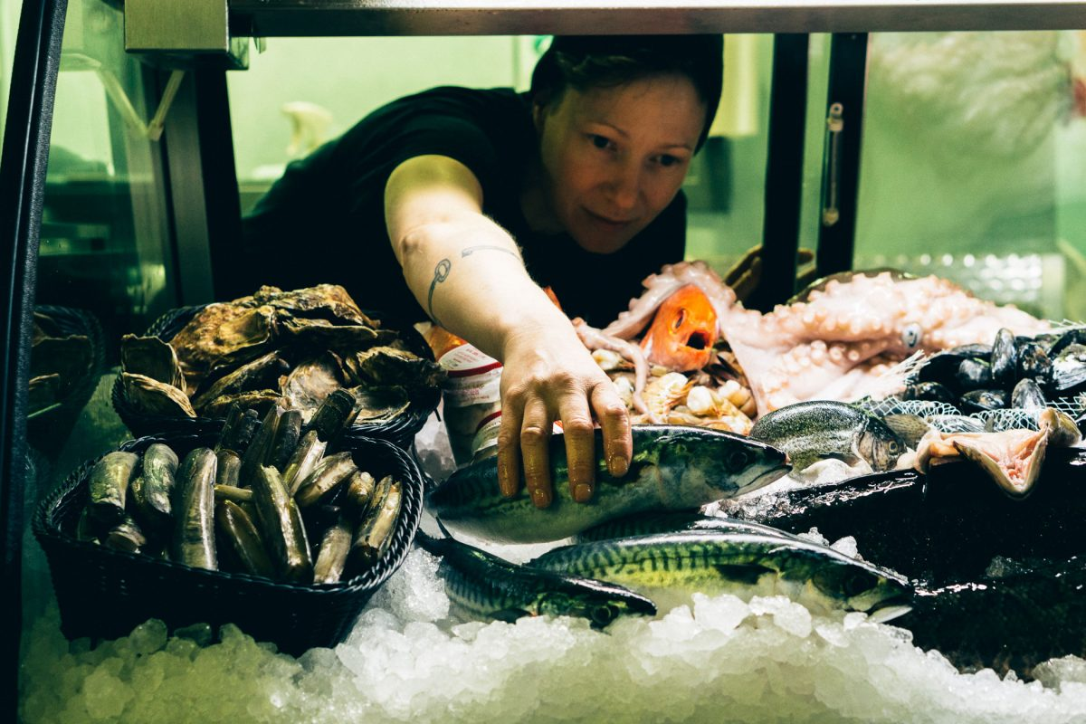 Fiona Lewis reaches for a fish in a display case at her shop, The District Fishwife. Photo courtesy of Fiona Lewis