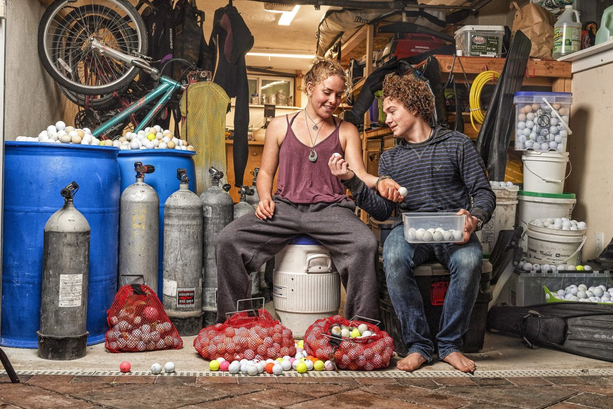 Alex Weber and Jack Johnston inspect some of the over 20,000 golf balls they've collected from the ocean and stored in Weber's garage. Photo by Robert Beck /Sports Illustrated/Getty Images