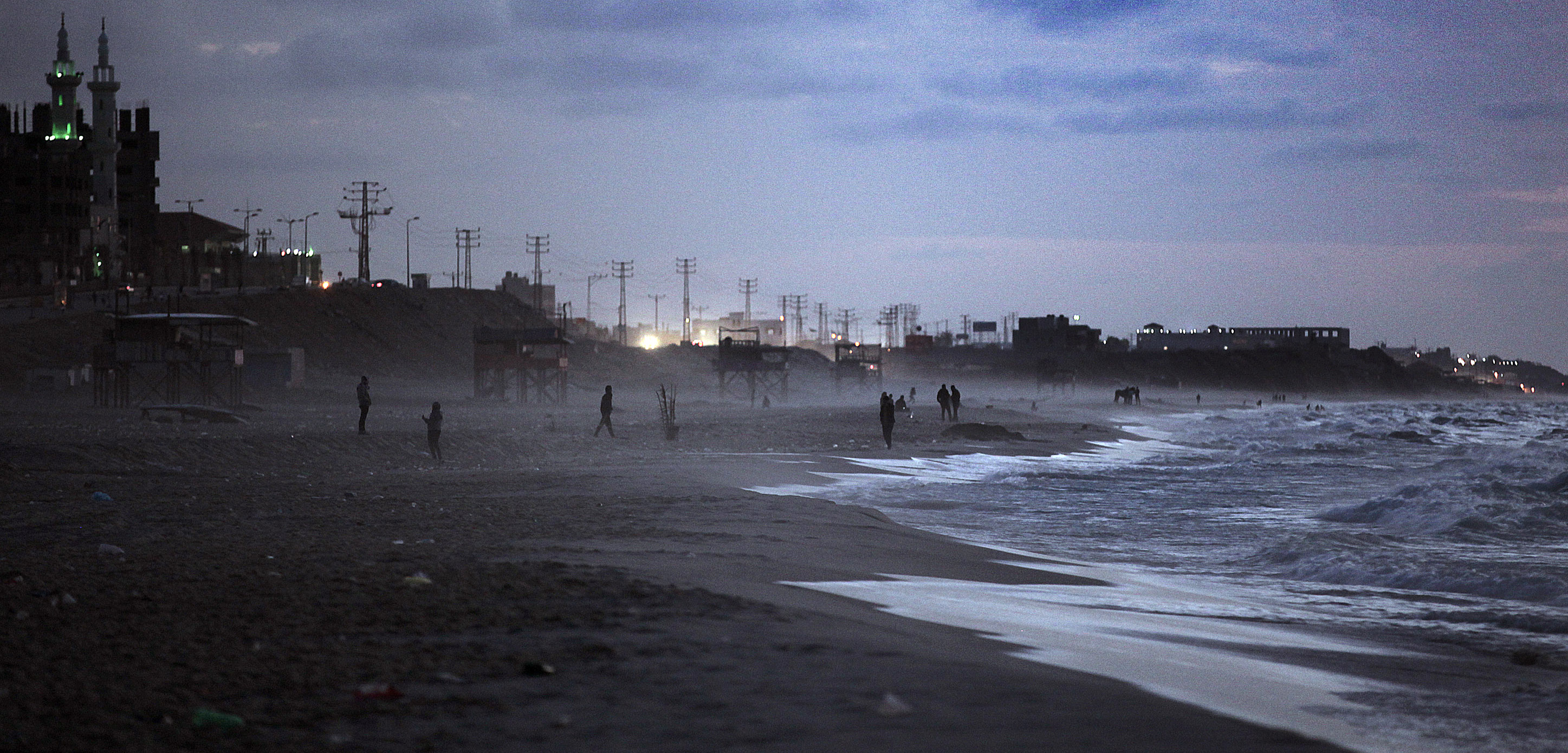 Palestinians stroll along a Gaza Strip beach. A complex political situation forces Gaza to dump sewage in the Mediterranean Sea. Photo by Ali Jadallah/ZUMA Press/Corbis