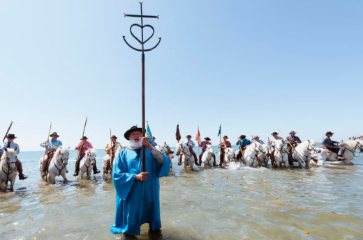 Men on white stallions splash into the Mediterranean Sea during the Gitan Pilgrimage in Saintes-Maries-de-la-Mer, France. Photo by Atlantide Phototravel/Corbis