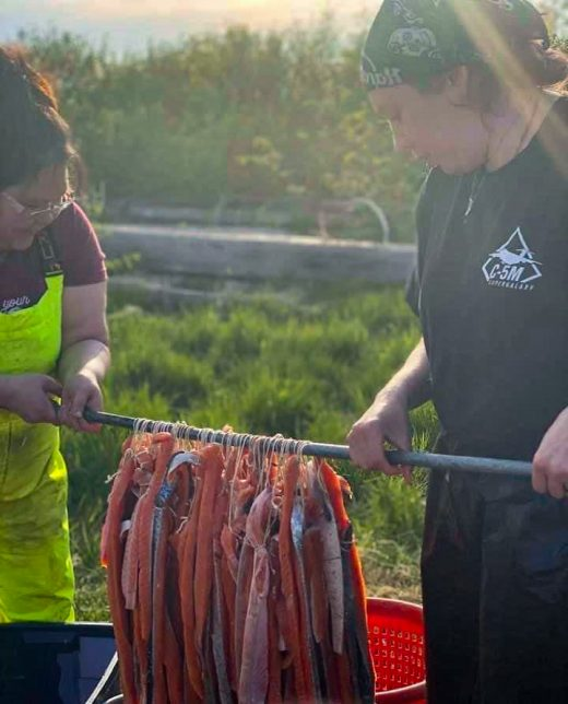 Jaclyn Christensen (left) and Tisha Kalmakoff dip strips of king salmon filets into a brine in preparation for the smokehouse. Photo courtesy of Jaclyn Christensen