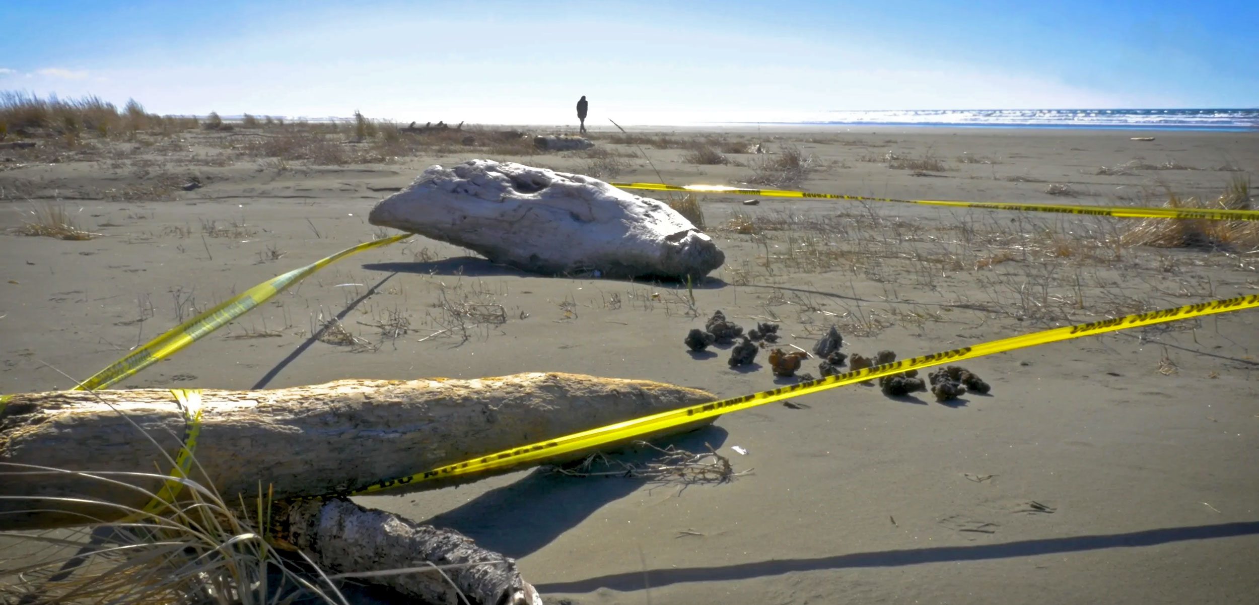 unexploded ordnances behind caution tape on the beach