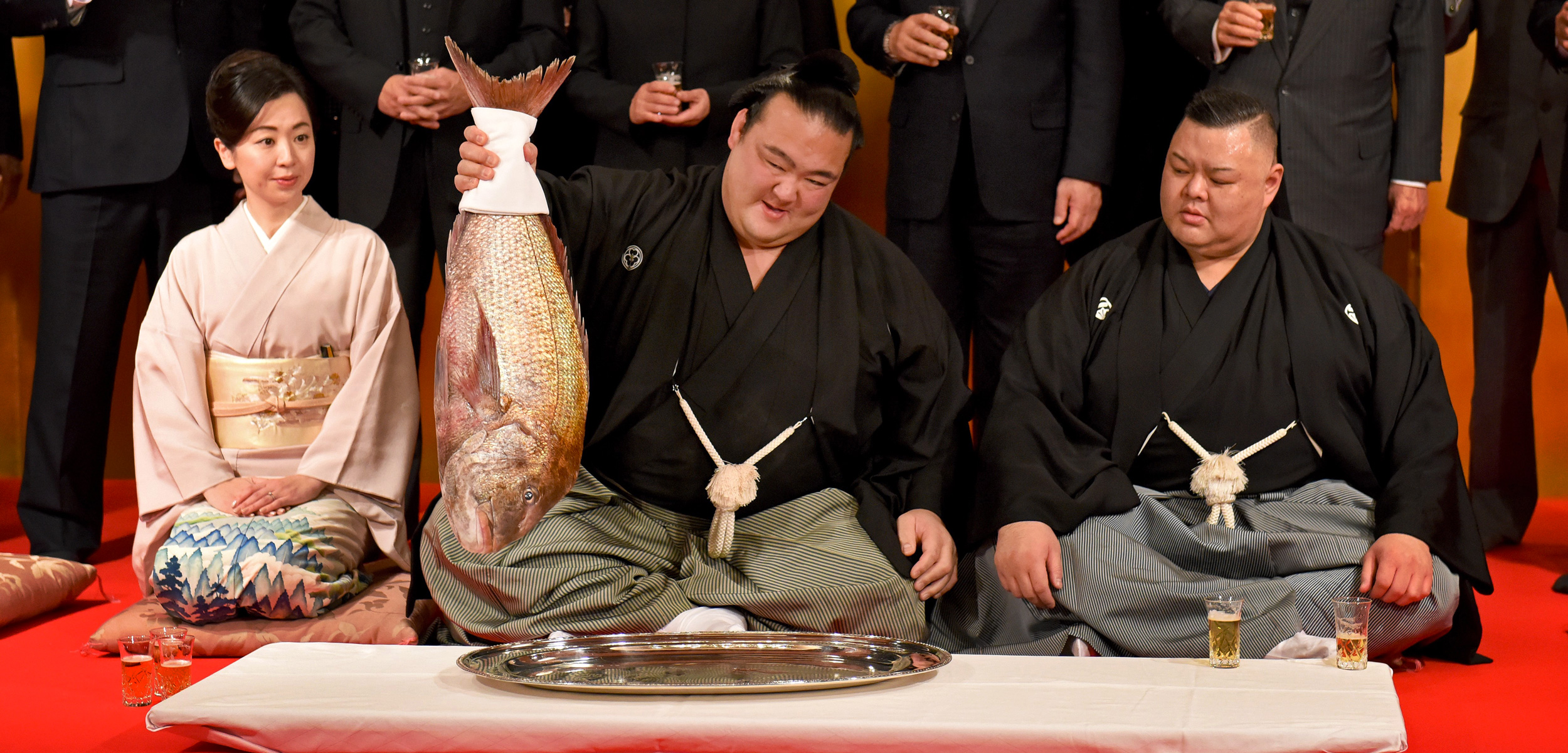 sumo wrestler Kisenosato Yutaka holds up a red seabream