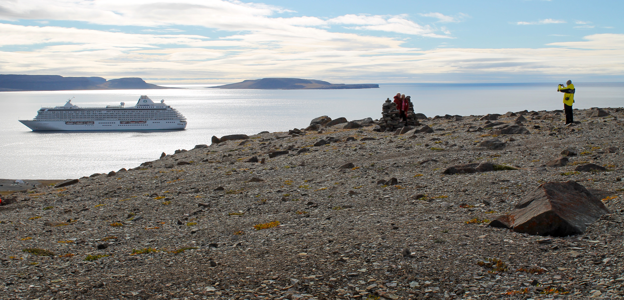 At a lookout on the north edge of Queens Bay, an expedition guide takes photos of two passengers in front of rock pilings overlooking the mouth of the bay that houses the Northwest Territories hamlet of Ulukhaktok and, for 24 hours, the Crystal Serenity. Photo by Elaine Anselmi