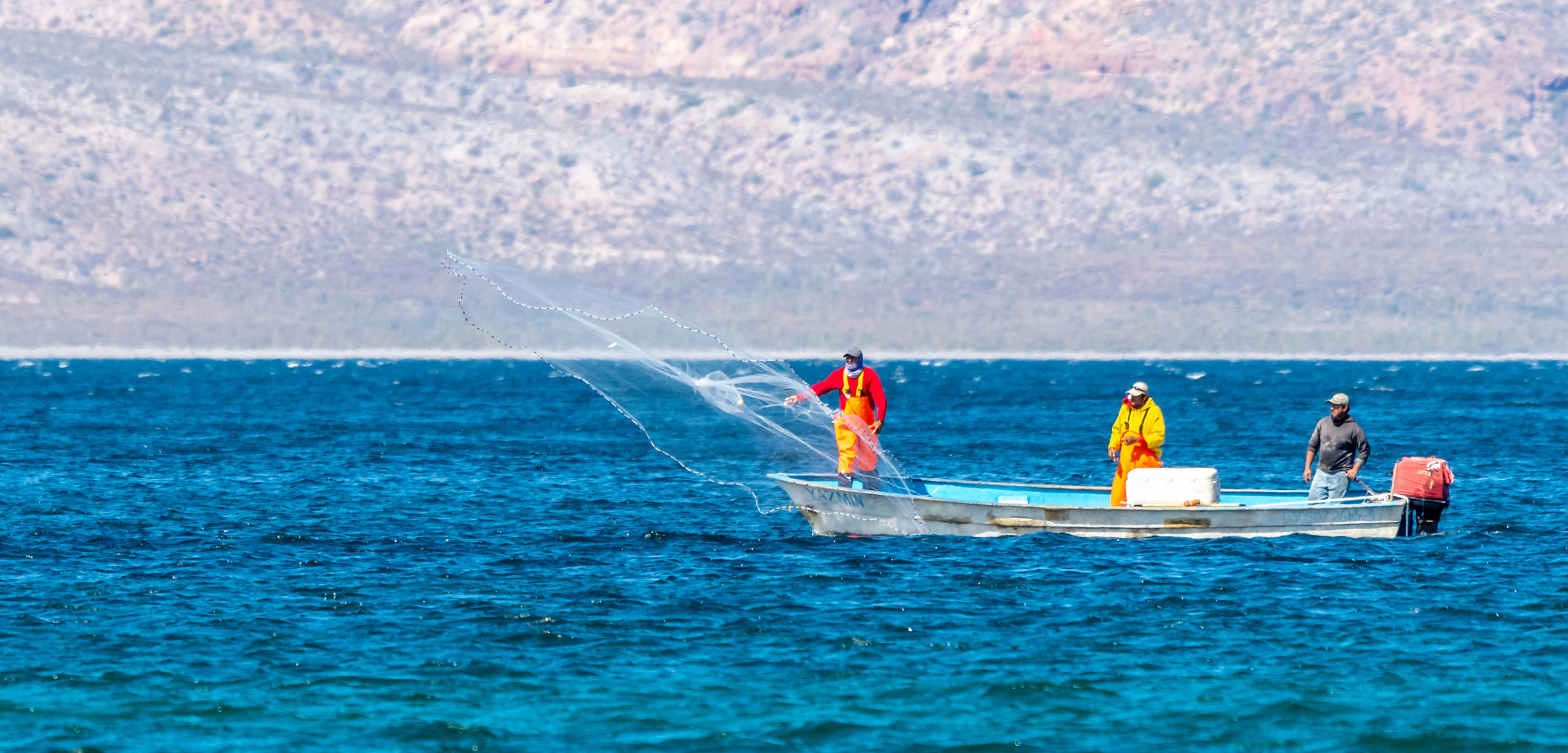 Fishermen in a small boat casting a fishing net in Baja California Sur, Mexico