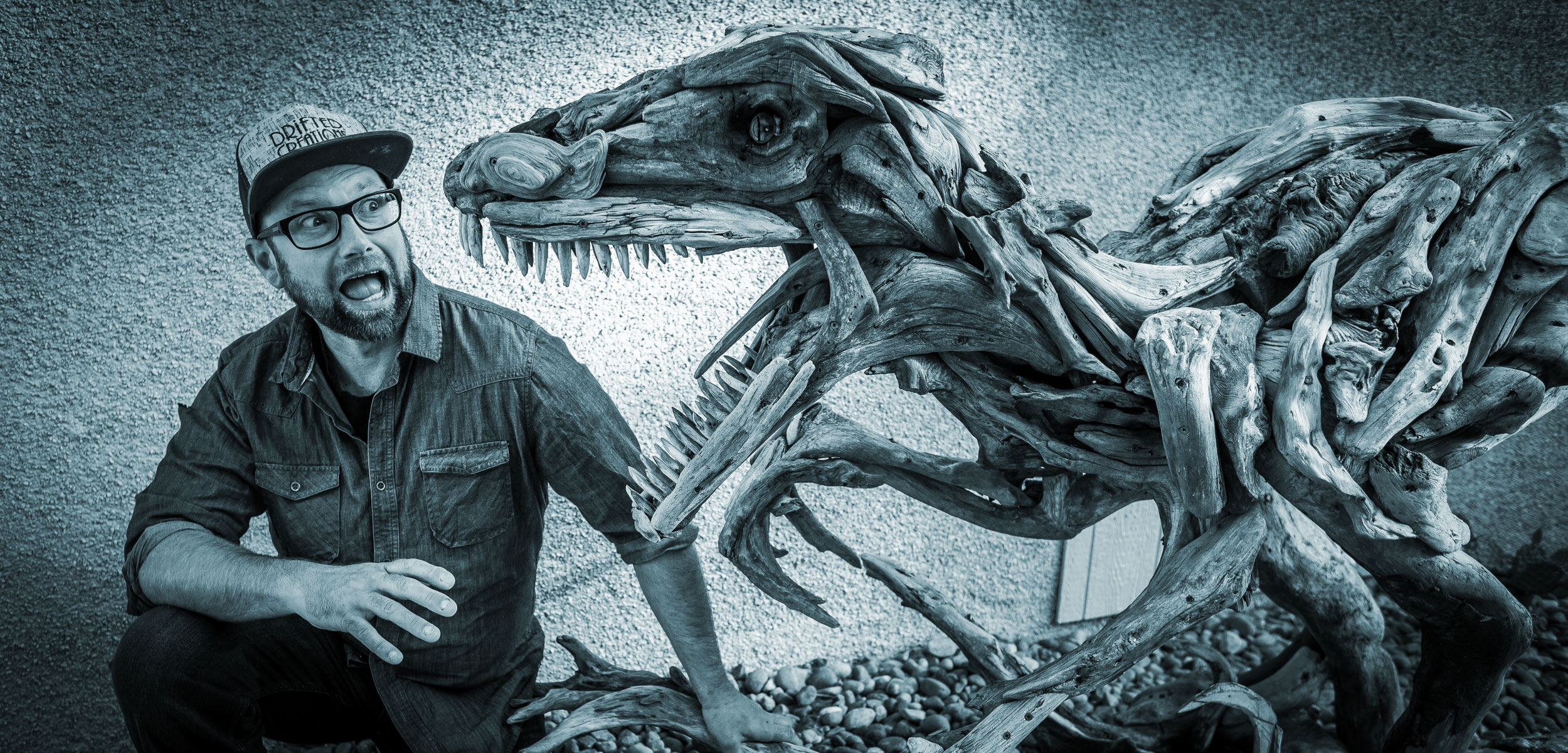 Driftwood artist Alex Witcombe poses with a Velociraptor sculpture