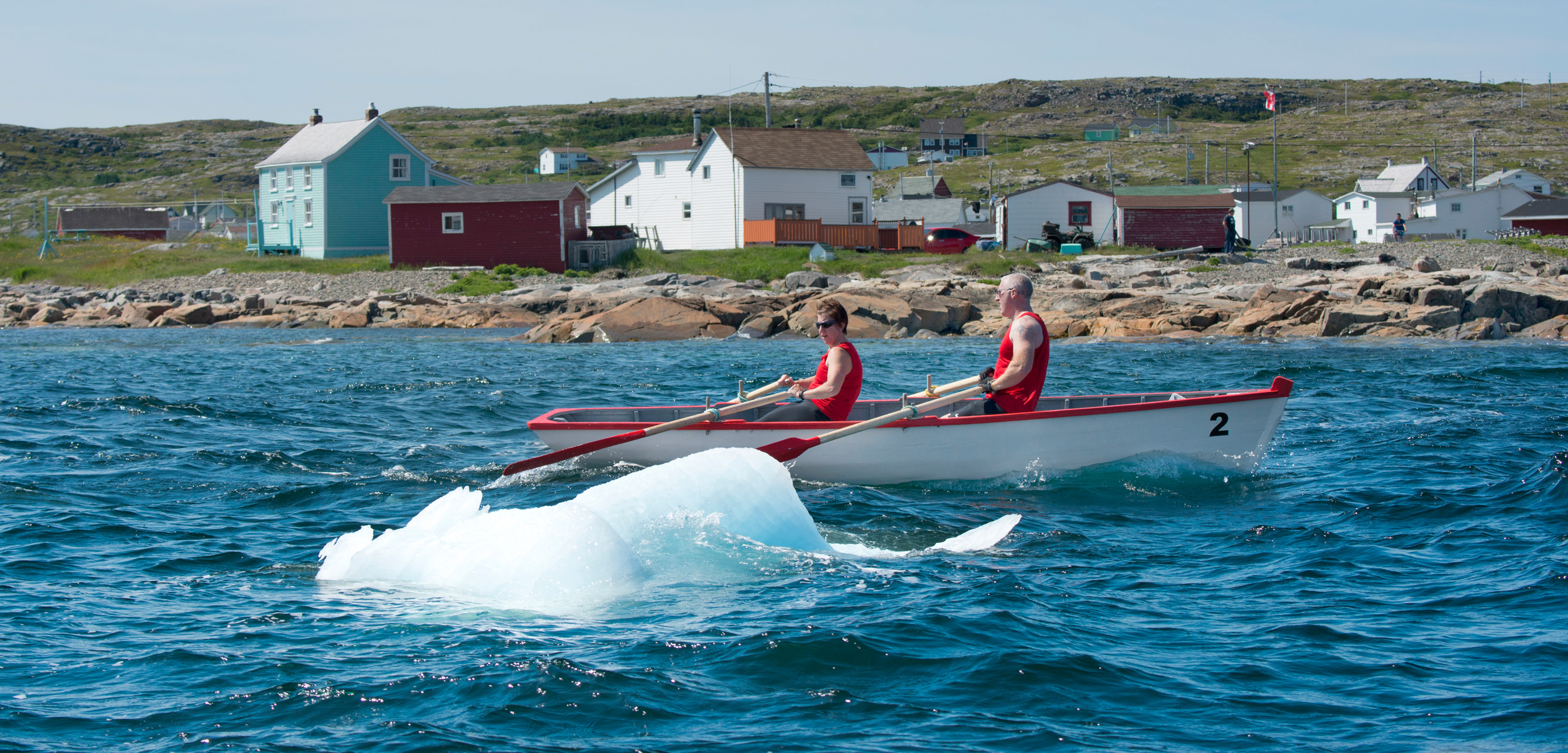 Racers in a punt dodge a small piece of iceberg—known locally as a growler—along the coast of Fogo Island, Newfoundland and Labrador.