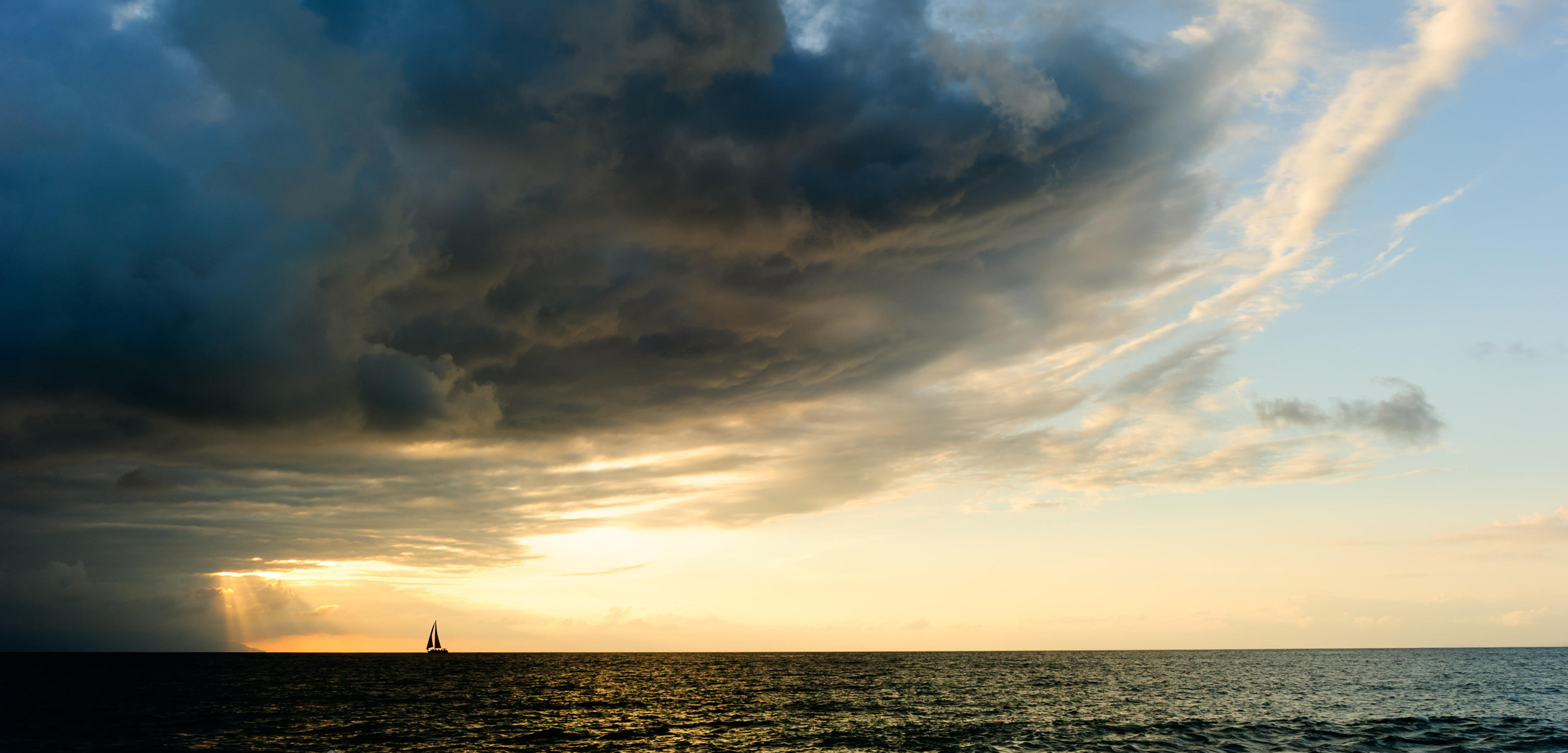 storm clouds and clear sky over ocean