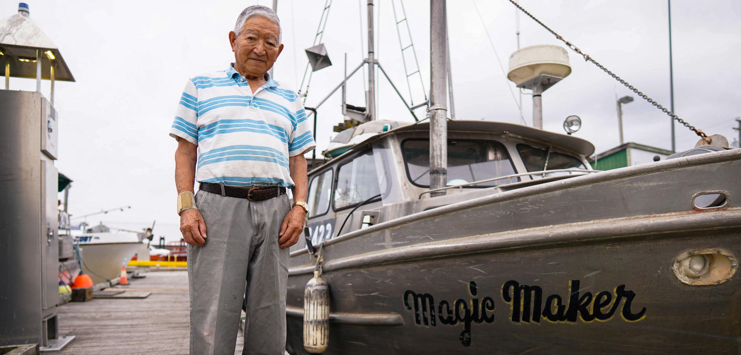 "Satoshi ""Sugar"" Hamada next to his boat"