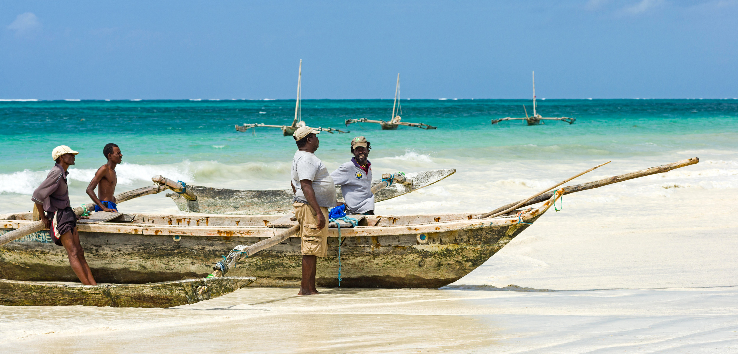 Fisherman with traditional dhow fishing boat at Diani beach, Kenya