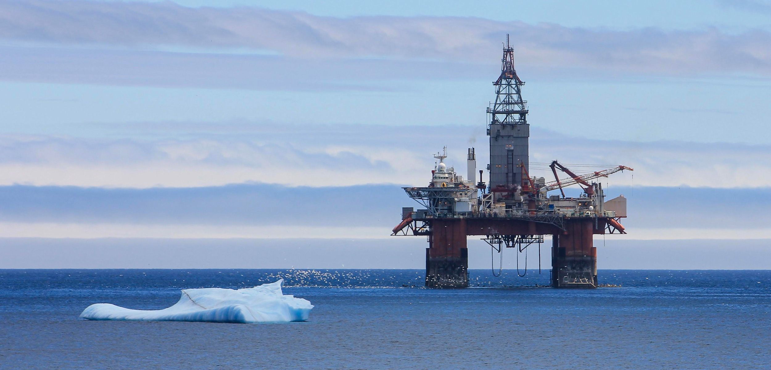 An Iceberg floating by an oil rig, Newfoundland and Labrador, Canada