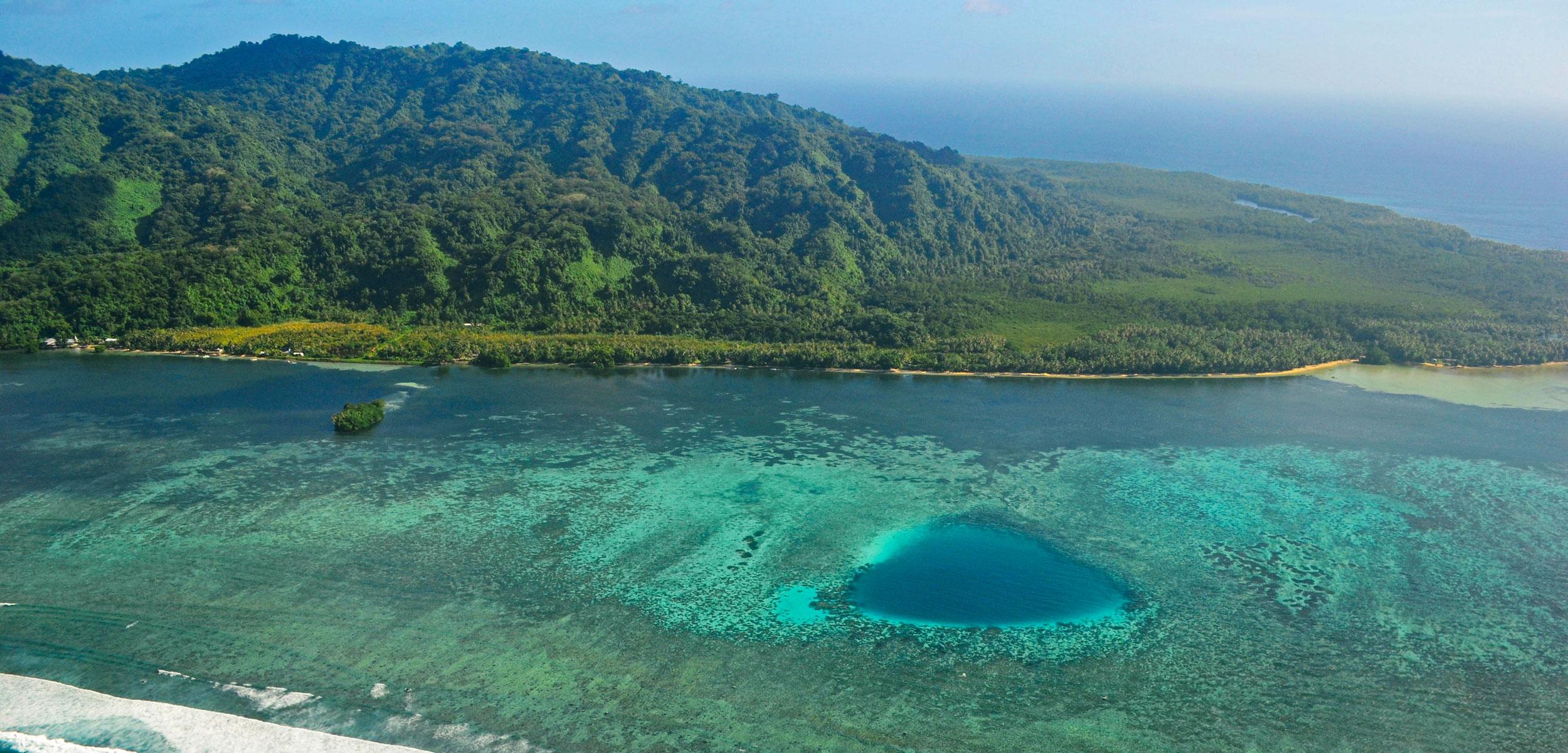 Green tropical landmass surrounded by light blue ocean
