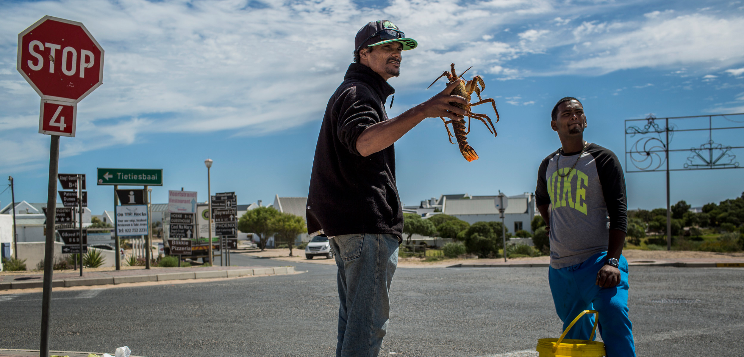At the entrance to Paternoster, South Africa, men openly sell illegally harvested crayfish. Photo by Charlie Shoemaker