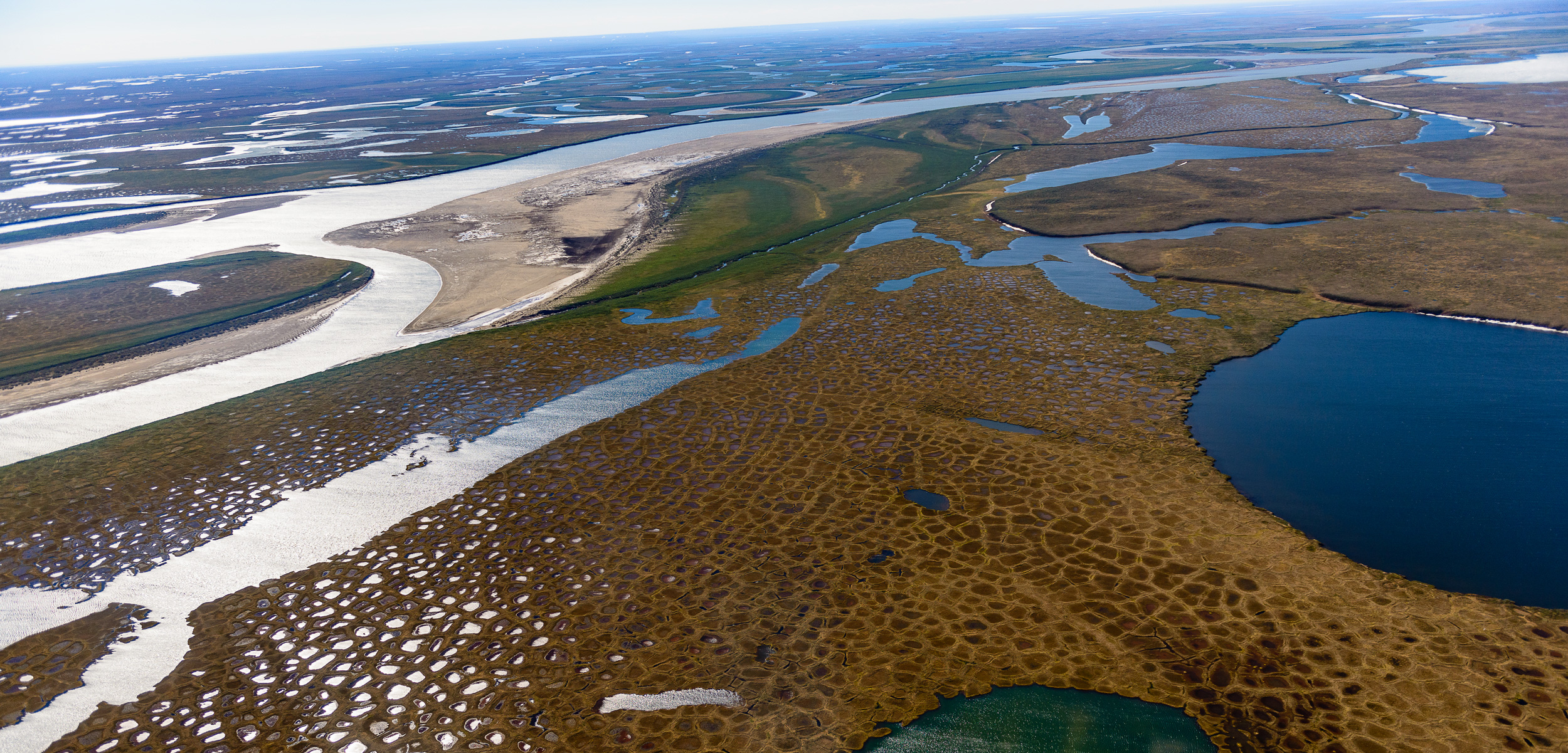 Thaw lakes and patterned ground surrounding the Colville River at the edge of the National Petroleum Reserve on Alaska's North Slope. More than 40 percent of the carbon dioxide entering the atmosphere from the Arctic comes from its surface waters.