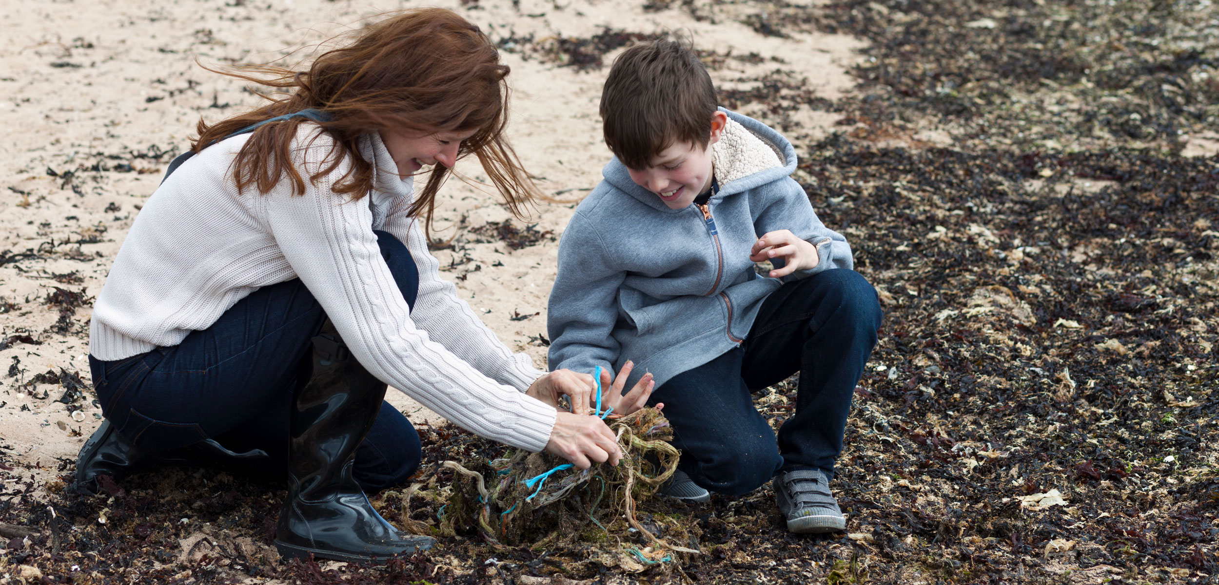 researcher and student collecting beach plastic in Scotland