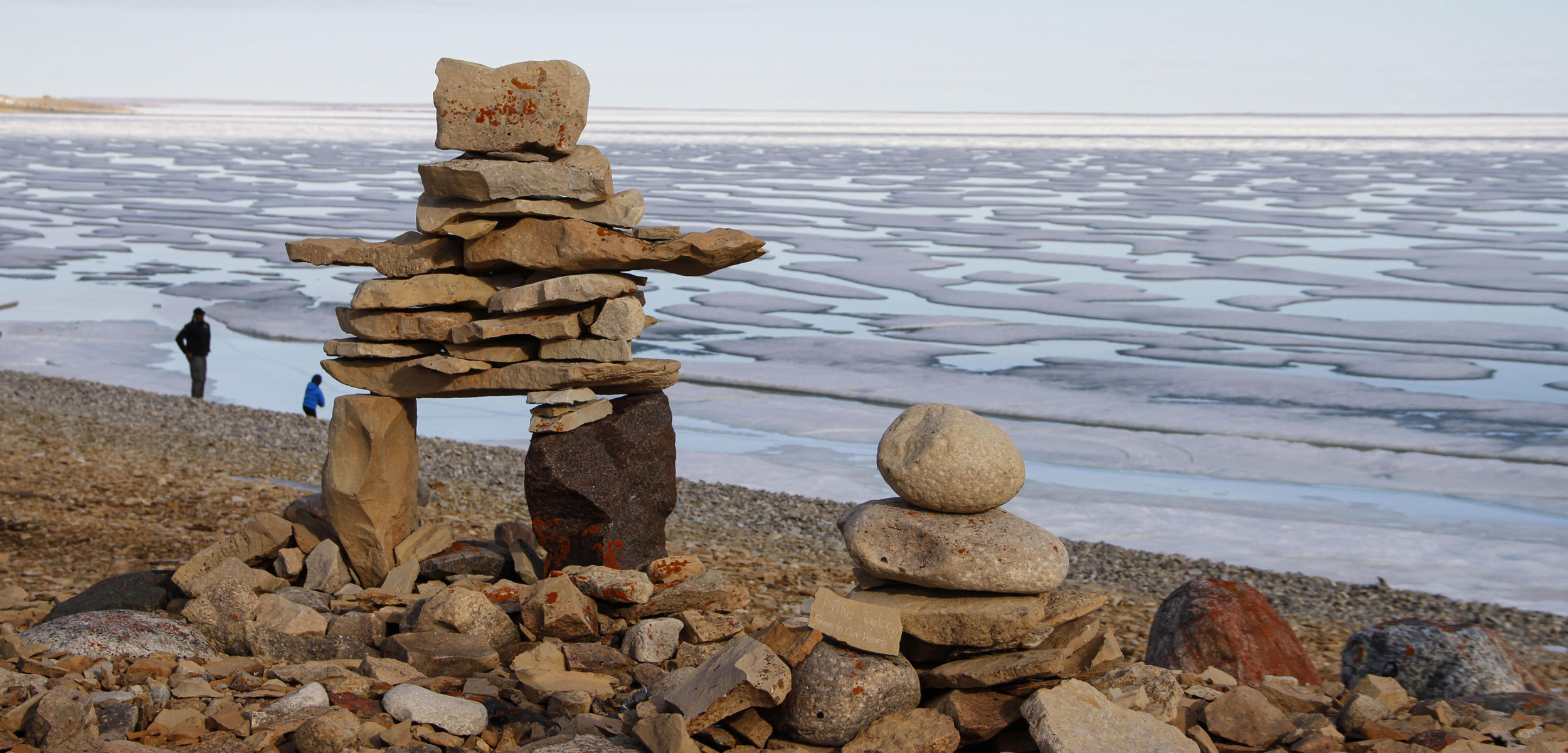 Inukshuk standing infront of a frozen sea