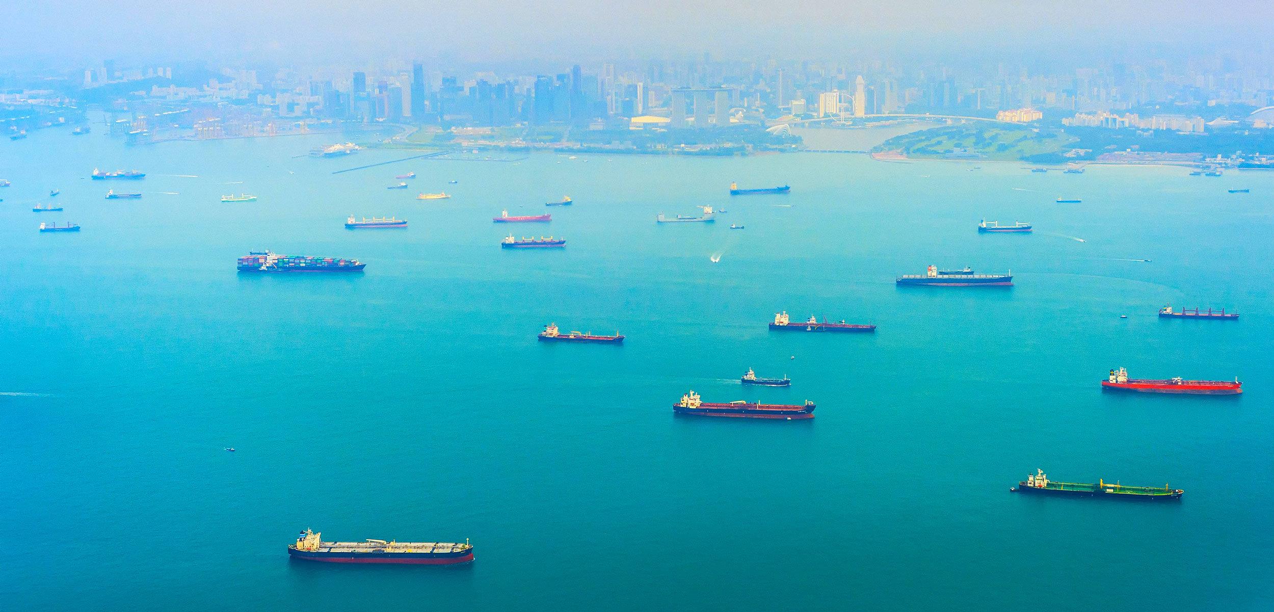 Aerial view of Singapore harbor with cargo ships, city in the background