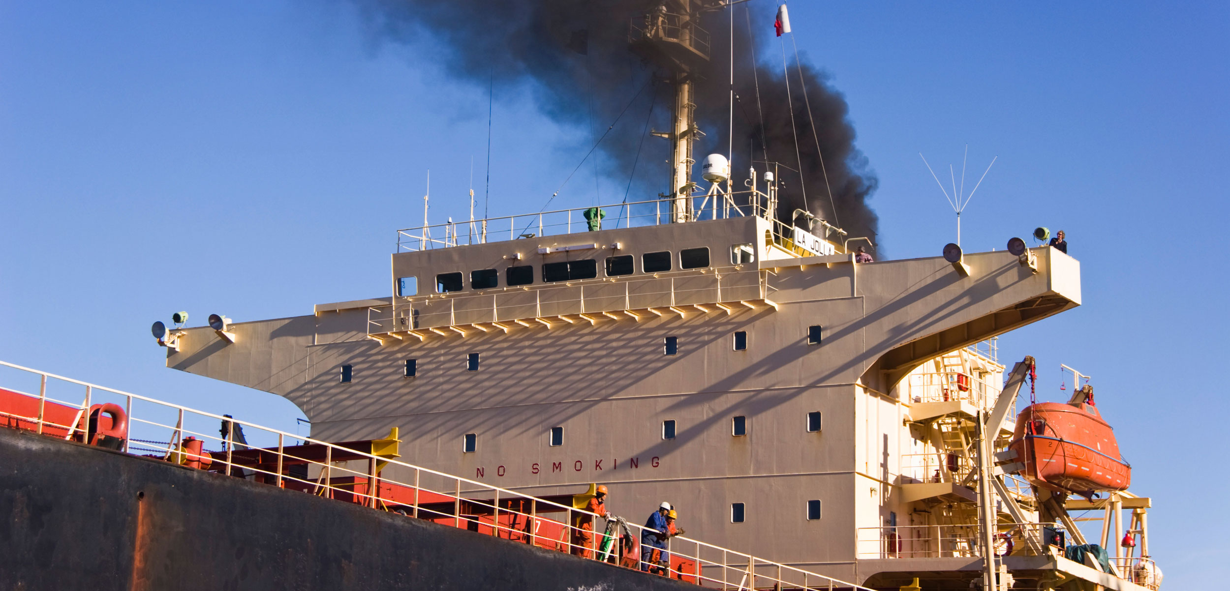 Black smoke rises from ship's funnel as the ship approaches the quay.