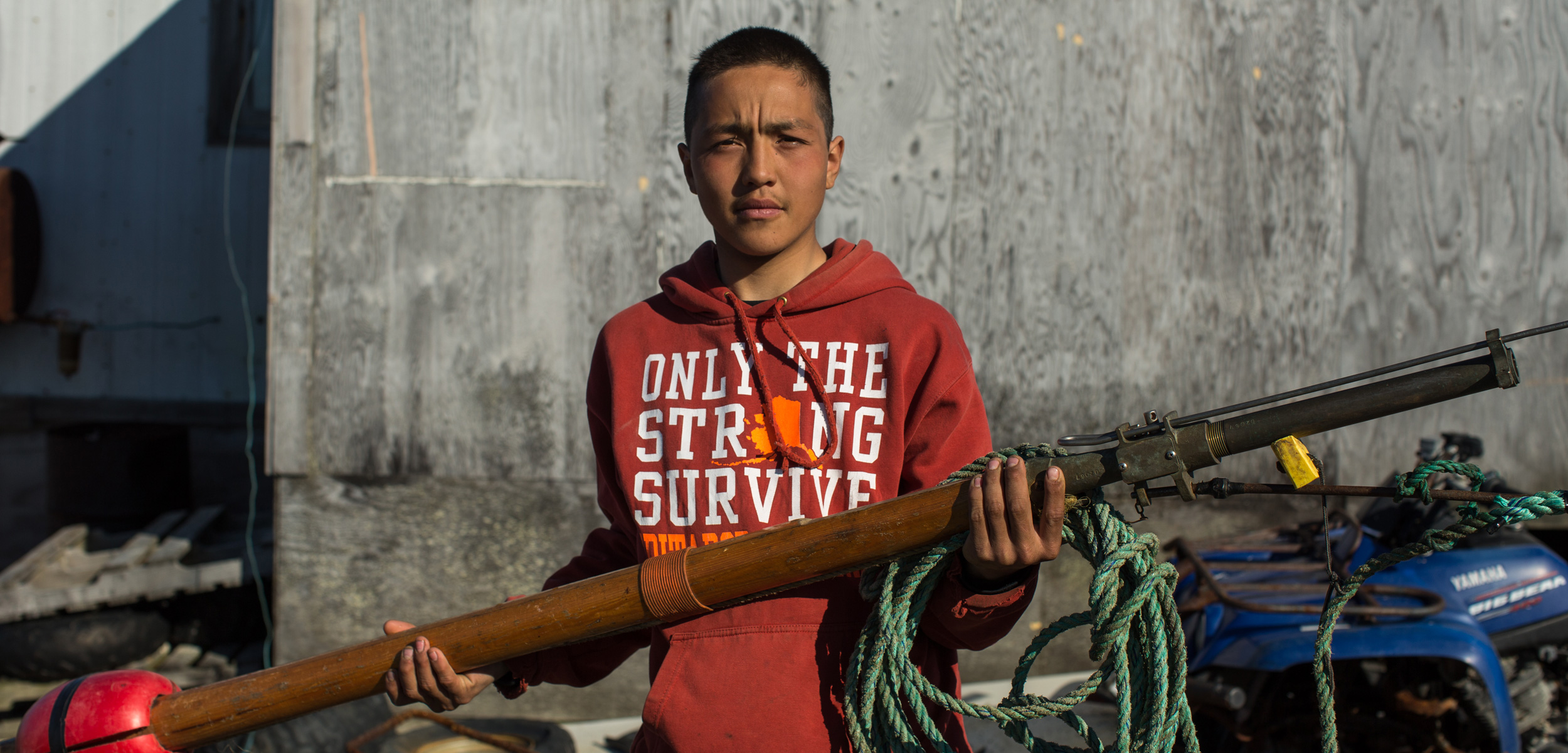 Chris Apassingok, 16, holds the darting gun he used to harpoon a whale this spring outside his family's home in Gambell, Alaska. Photo by Ash Adams