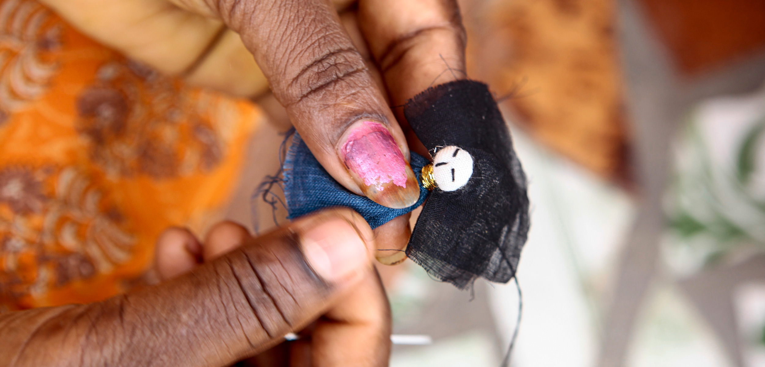 woman's hands sewing doll