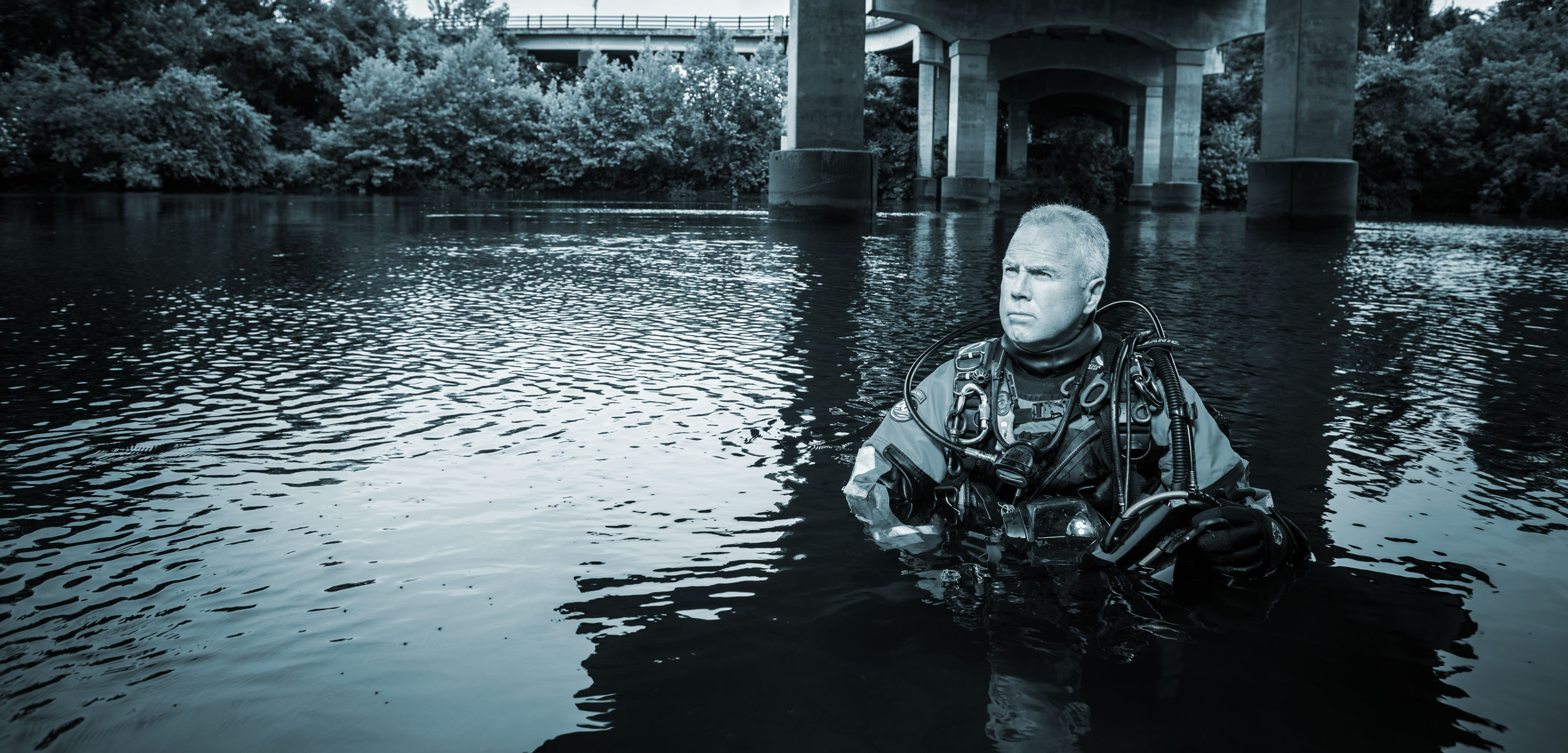 Underwater Investigator Mike Berry poses in a river under a bridge