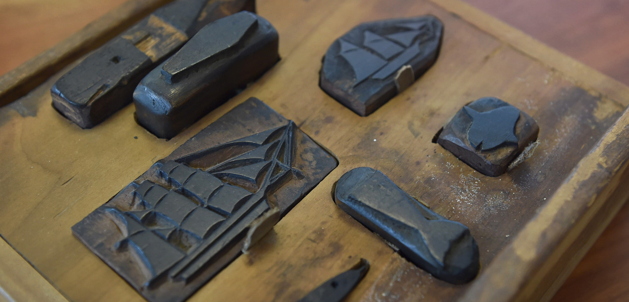 This collection of seven stamps is one of the most elaborate examples of carved stamps used by 19th-century whalers to record details of their voyage. The set includes a whale, a three-masted bark, a schooner, a whale's flukes, an unidentified cetacean, a sunfish, and a coffin. Photo by Nelson Mare