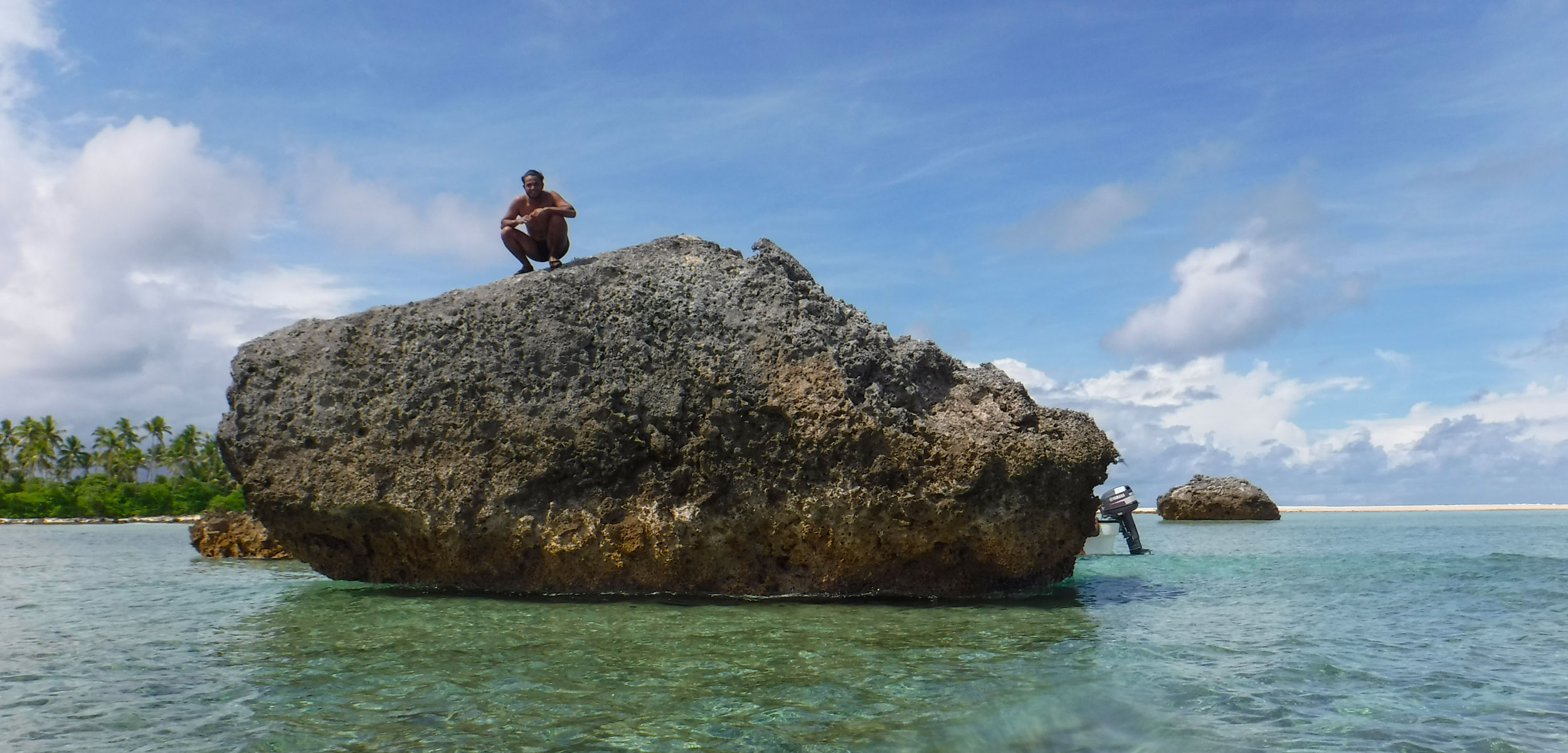 Person standing on large rock in teal water