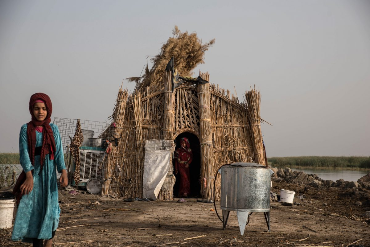 Inas (left) and Baneen Ali emerge from the family home in the Central Marsh in the early morning. Photo by Emilienne Malfatto