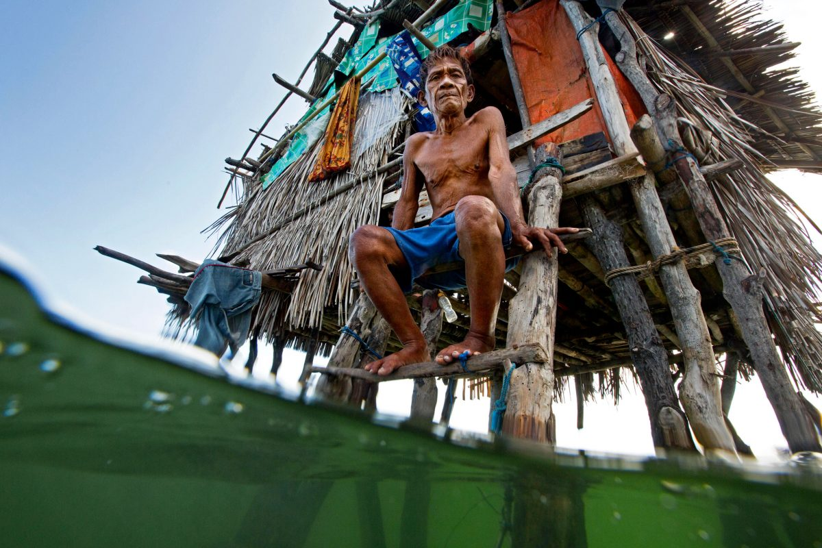 Bajau fisher sits in front of his home