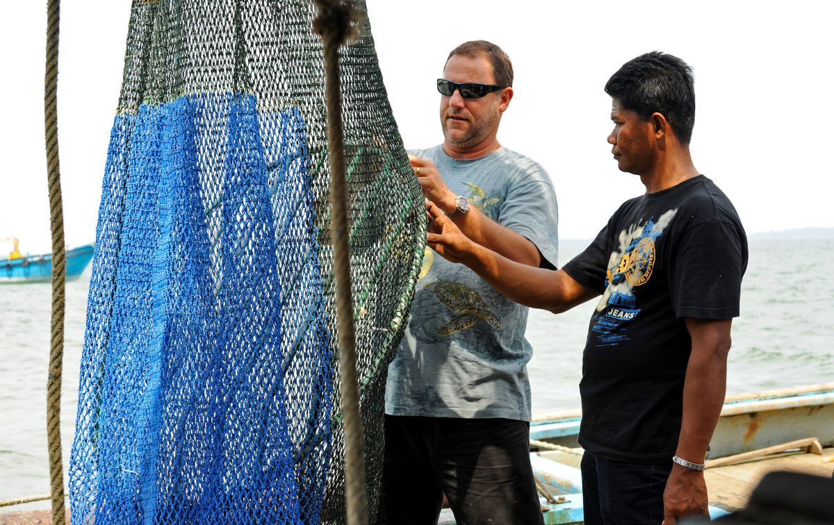 Nicolas Pilcher (left), from Malaysia's Marine Research Foundation, shows a fisherman how to install a turtle excluder device