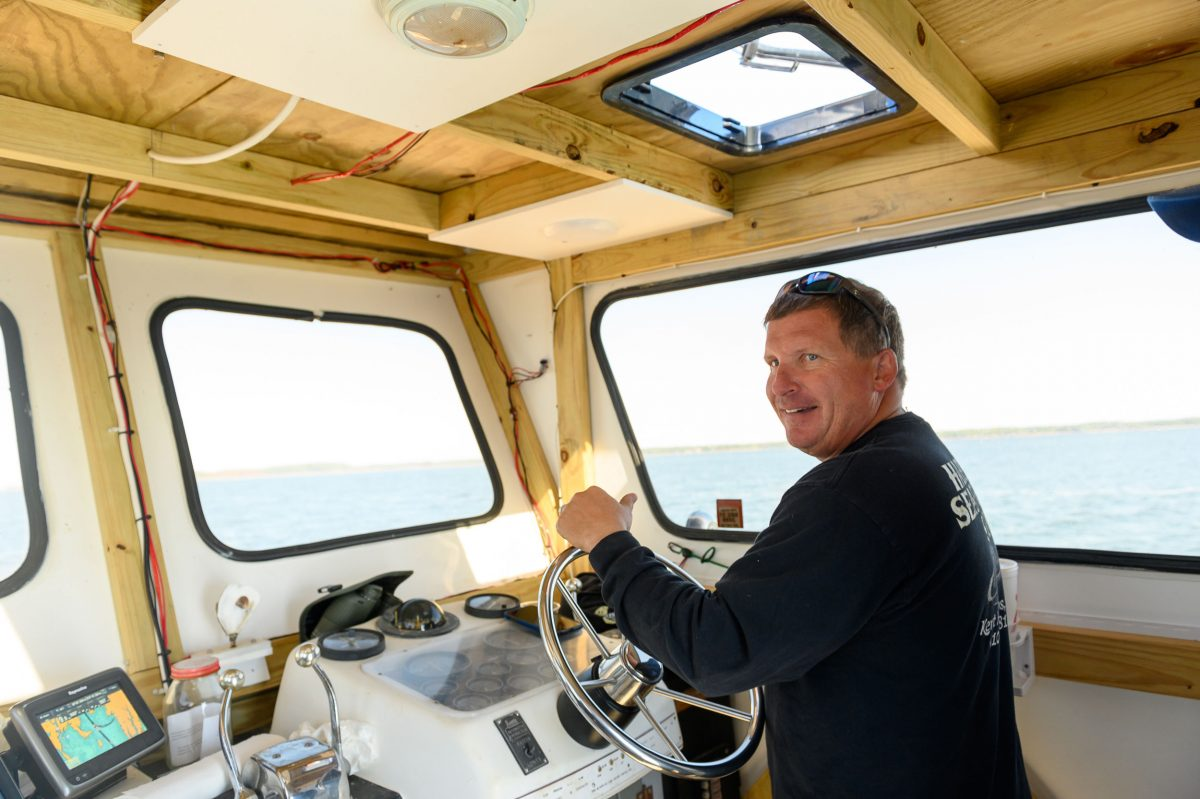 Jason Ruth, owner of Maryland-based Harris Seafood Company, at the helm of his boat on the Chesapeake Bay. Photo by Erin Scott