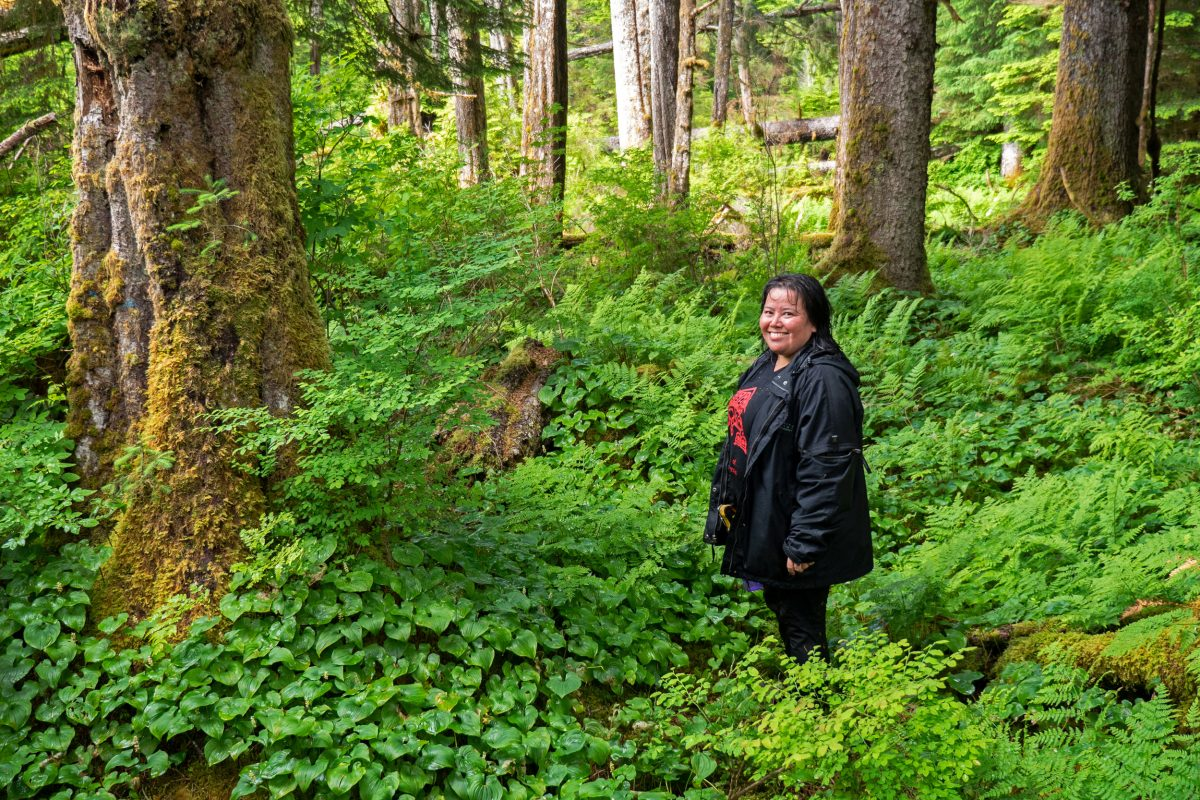 Jennifer Walkus, a member of the Wuikinuxv Nation's bear working group, hikes through the woods in the nation's territory.